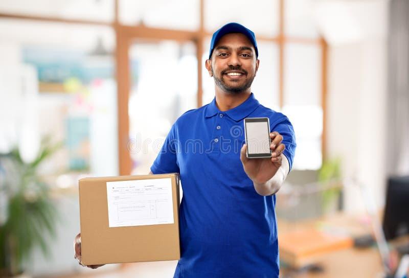 Indische leveringsmens met smartphone en pakketdoos stock fotografie