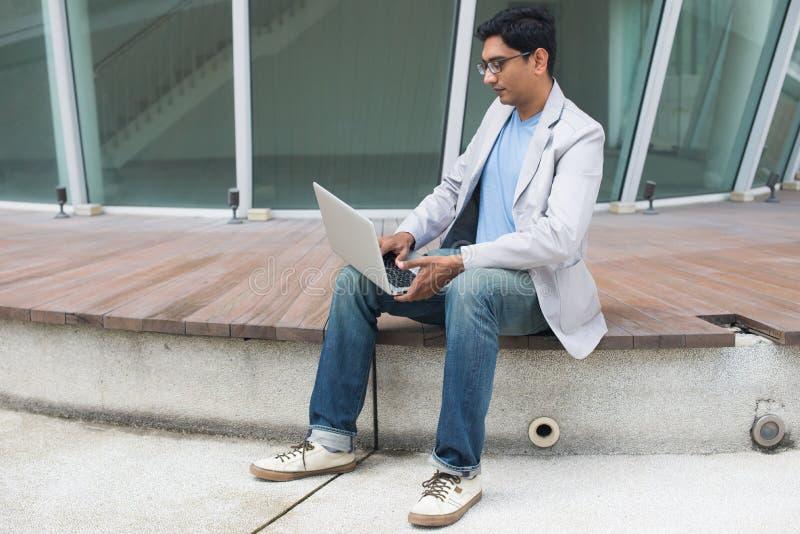 Indische mannelijke gebruikende laptop stock afbeelding