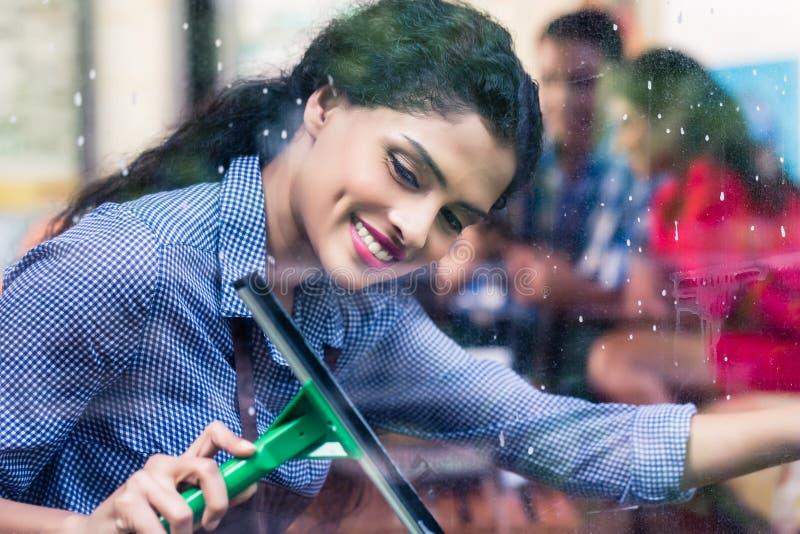 Indische meisjes schoonmakende vensters royalty-vrije stock afbeeldingen