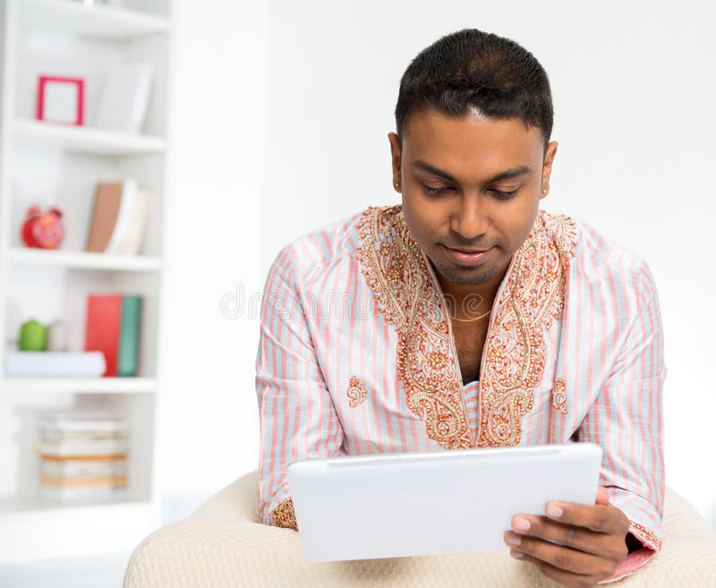 Indische mens die digitale tabletpc thuis met behulp van. royalty-vrije stock afbeelding
