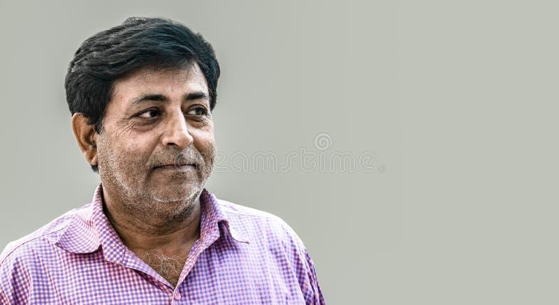 Indische mens die op middelbare leeftijd uitdrukking die van tevredenheid geven, purper controleoverhemd dragen Het kenmerken van royalty-vrije stock afbeelding