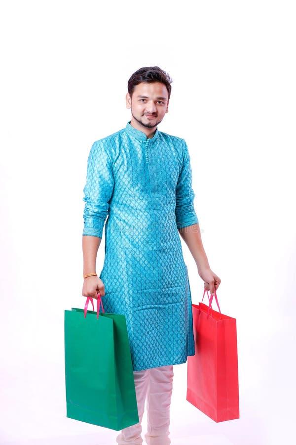Indische mens in etnische die slijtage met het winkelen zakken, over witte achtergrond wordt geïsoleerd stock foto