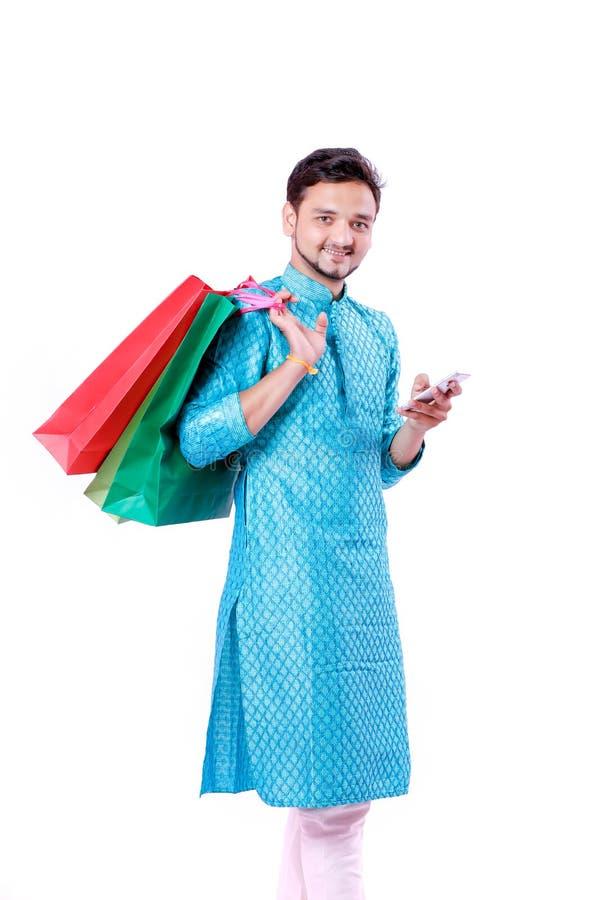Indische mens in etnische slijtage met het winkelen zakken en het tonen van het mobiele die scherm, over witte achtergrond wordt  stock foto's
