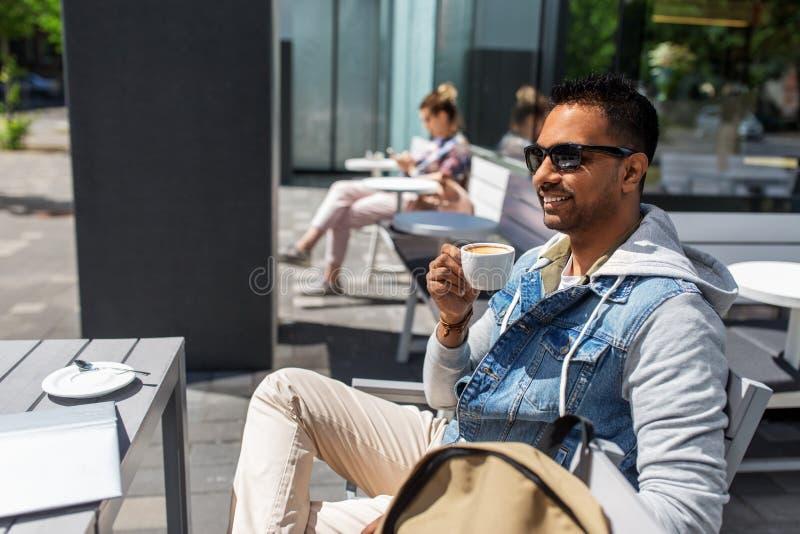 Indische mens het drinken koffie bij de koffie van de stadsstraat royalty-vrije stock afbeelding