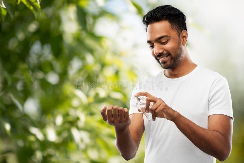 Indische mens met parfum over natuurlijke achtergrond stock foto's