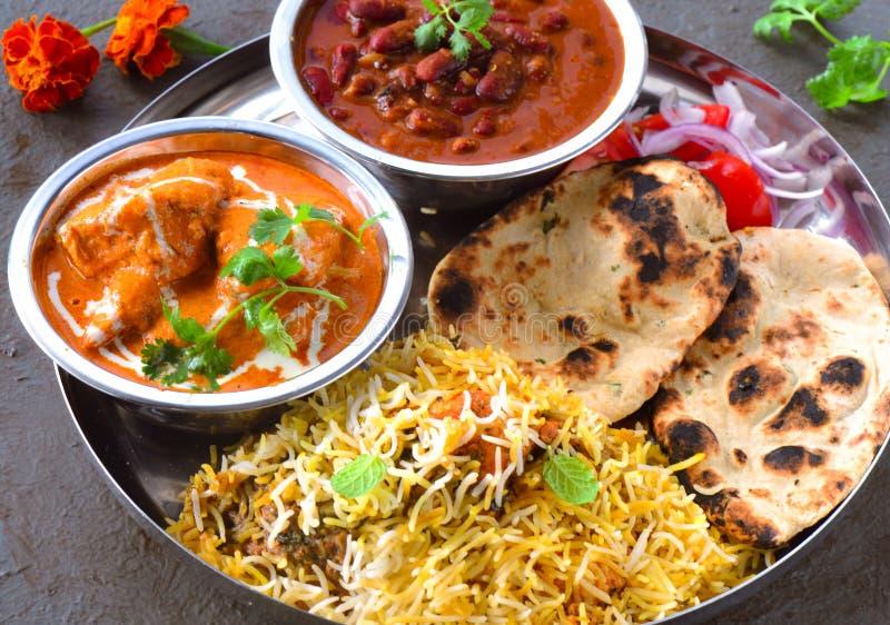Indische niet vegetarische Maaltijd - Boterkip, rajma, biryani met roti en salade stock afbeeldingen