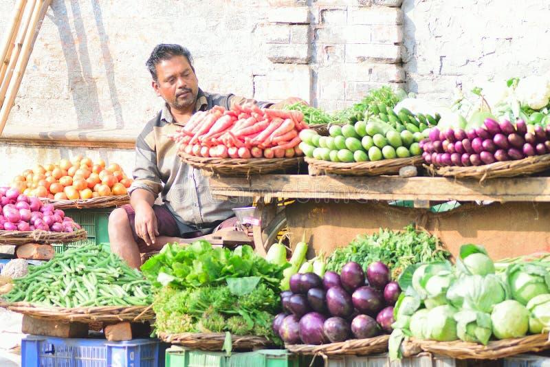 Indische plantaardige verkoper bij voedselmarkt in Varanasi, India stock foto's