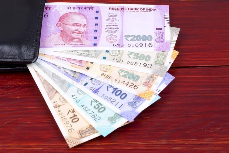 Indische Rupie in der schwarzen Geldbörse stockfotografie