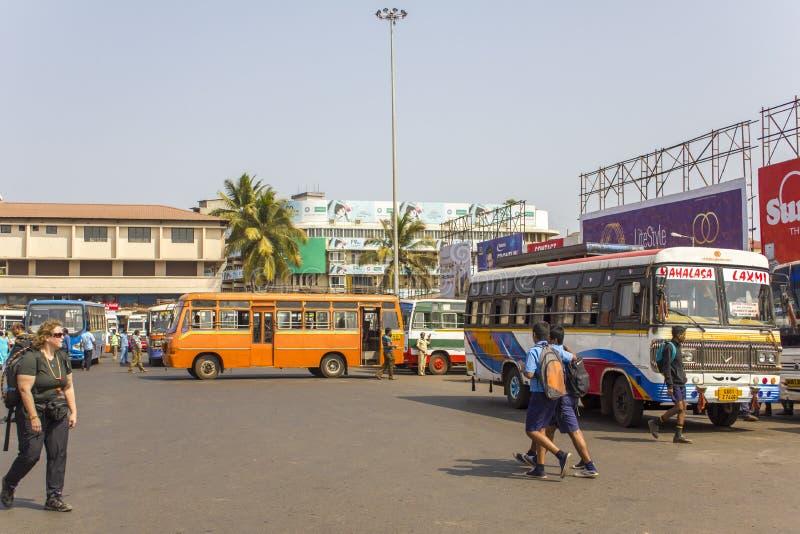 Indische schoolkinderen op de achtergrond van multi-colored bussen bij het busstation op royalty-vrije stock afbeeldingen