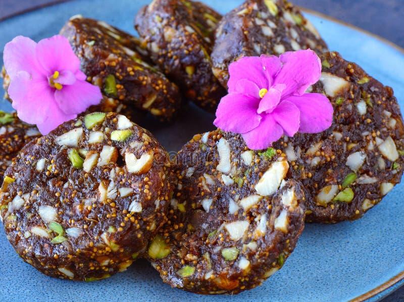 Indische Snoepjes in blauwe ceramische plaat - geen suiker Anjeer of fig. rolt stock afbeelding