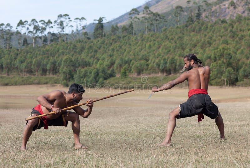 Indische vechters die Wapengevecht uitvoeren tijdens Echtelijke de kunstdemonstratie van Kalaripayattu in Kerala, India royalty-vrije stock foto's