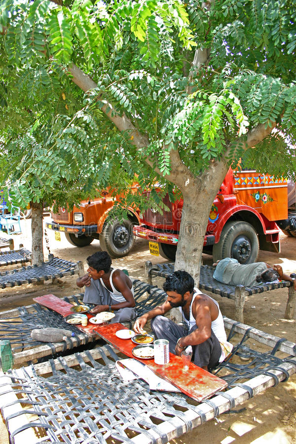Indische vrachtwagenchauffeurs die uit op de kant van de wegrestaurants eten in wegen met hun vrachtwagens stock foto's