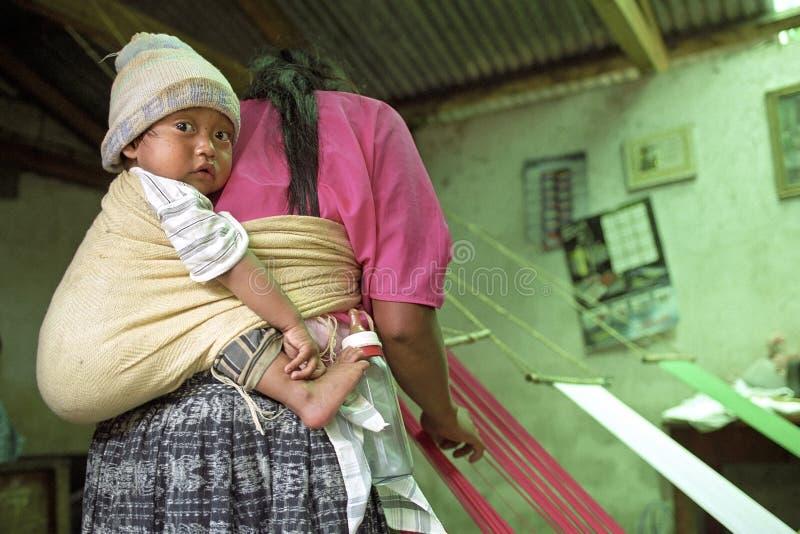 Indische vrouw bij wevend weefgetouw met kind op rug stock foto's