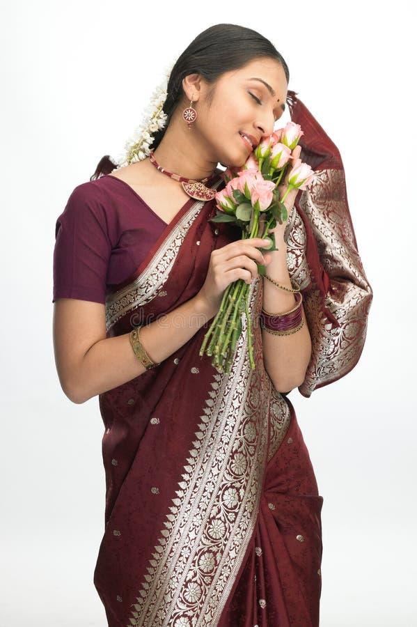 Indische vrouw die de rozen voelt royalty-vrije stock afbeeldingen