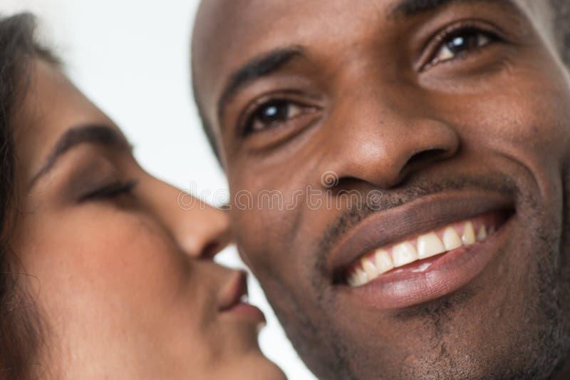 Indische vrouw die de zwarte mens op wang kussen stock afbeelding
