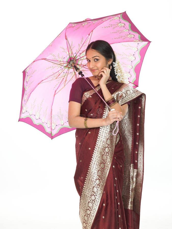 Indische vrouw met paraplu die over cel spreekt royalty-vrije stock fotografie