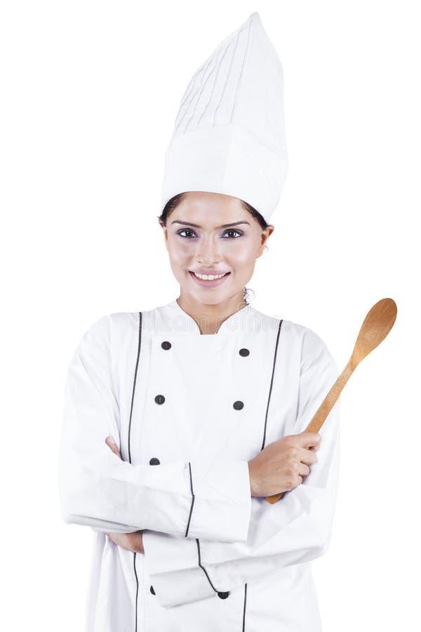 Indische vrouwelijke chef-kok die houten lepel houden royalty-vrije stock afbeeldingen