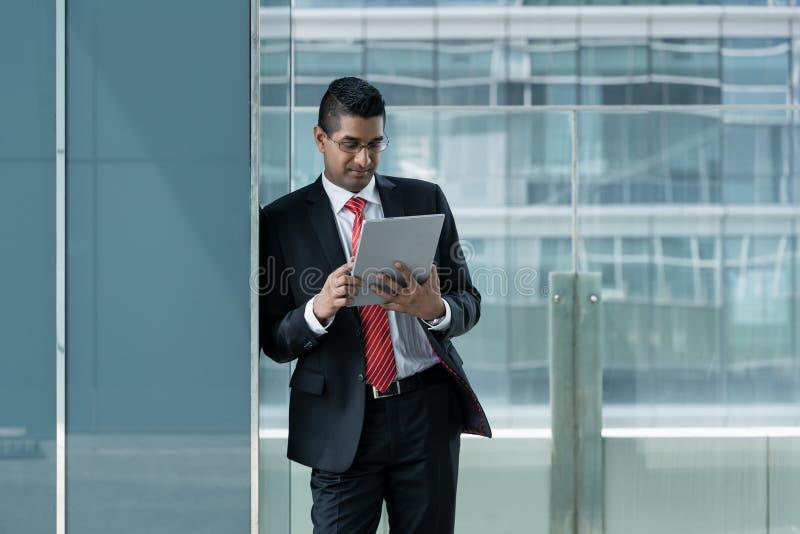 Indische zakenman die een tabletpc binnen met behulp van stock foto