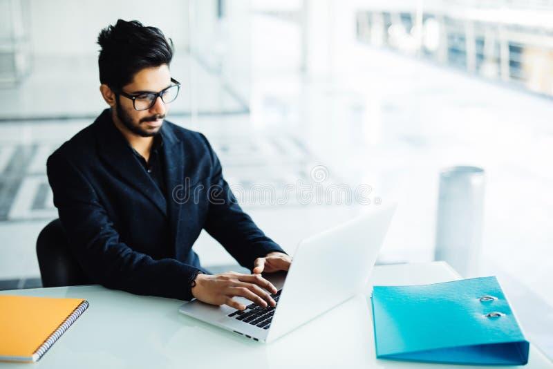 Indische zakenman Zekere zakenman die aan zijn laptop in het bureau werken stock fotografie