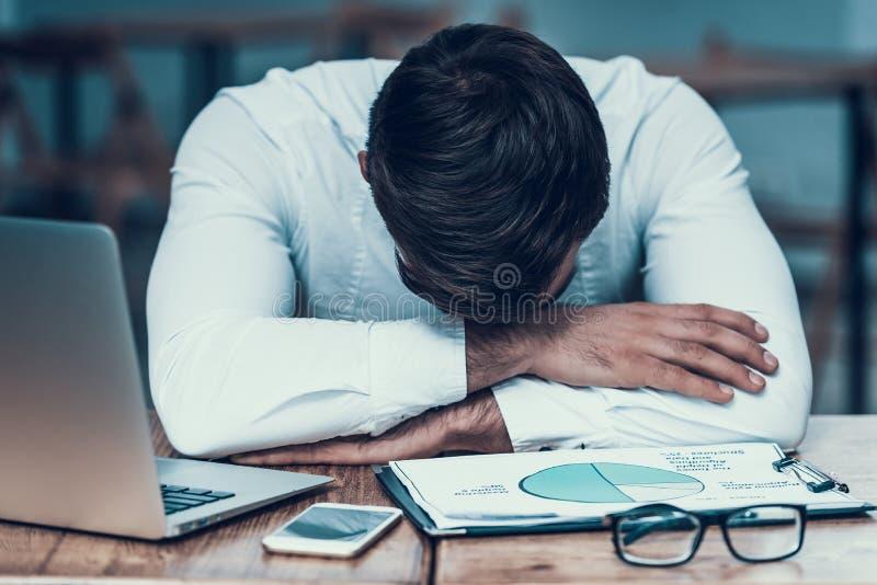 Indische zakenmanslaap op het werk, zitting bij lijst stock afbeelding