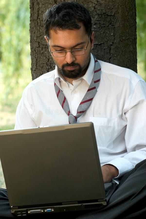 Indische zitting met laptop royalty-vrije stock afbeelding