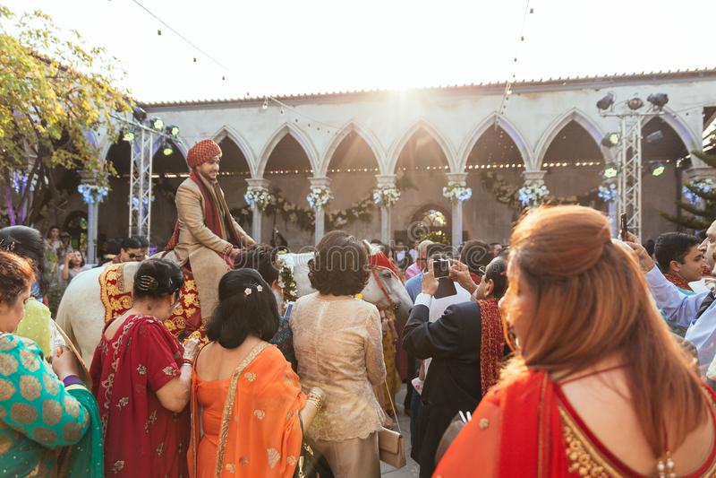 Indischer Bräutigam, der Schimmel zum Hochzeitszeremonieplatz mit Gästen in Bangkok, Thailand reinigt lizenzfreie stockbilder