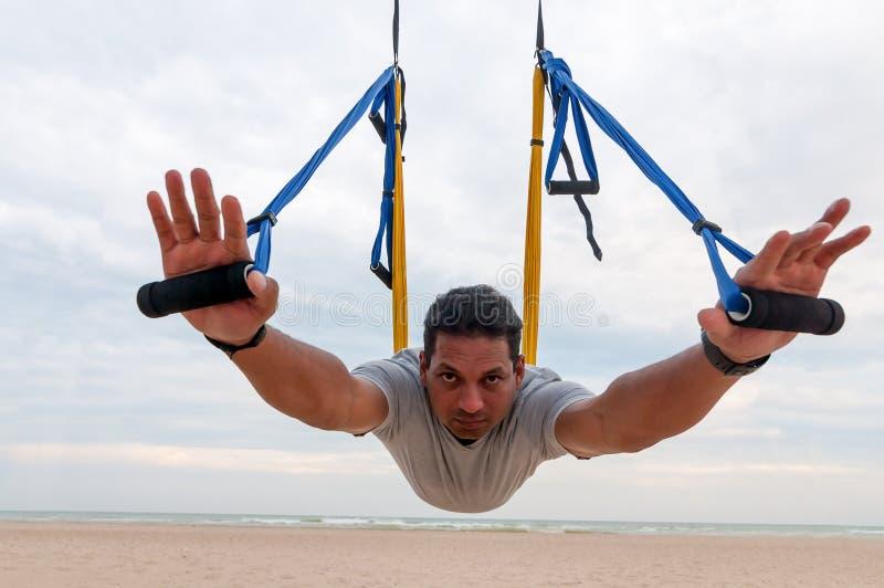 Indischer Esprit des jungen Mannes der Ethnie, den ein starker Körper, der Yoga tut oder Fliegeyoga auf dem Seehintergrund ausübt lizenzfreie stockbilder