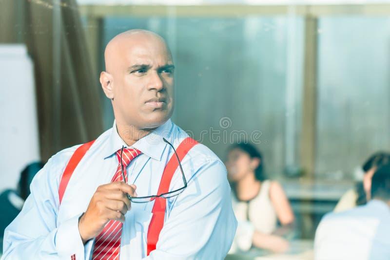 Indischer Geschäftsmann, der am Bürofenster denkt lizenzfreies stockfoto