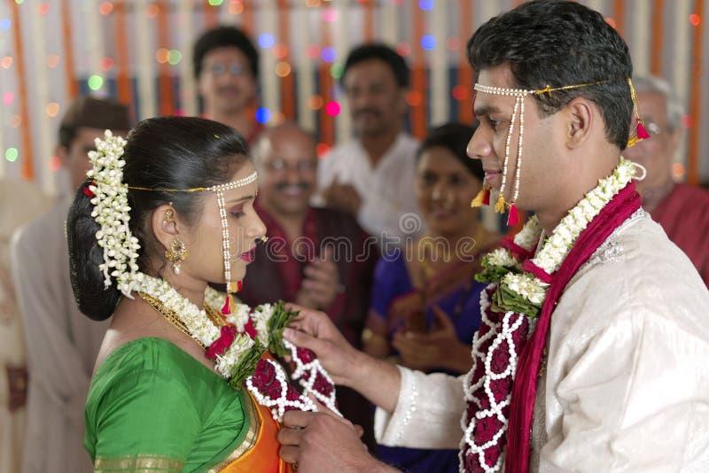 Indischer hindischer Bräutigam, der Braut betrachtet und Girlande in der Maharashtrahochzeit austauscht stockbilder