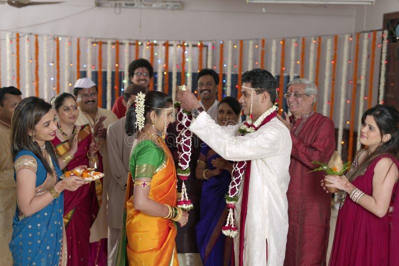 Indischer hindischer Bräutigam, der Braut betrachtet und Girlande in der Maharashtrahochzeit austauscht stockfotos