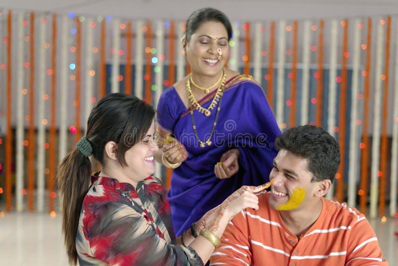 Indischer hindischer Bräutigam mit Gelbwurzpaste auf Gesicht mit Mutter lizenzfreie stockfotografie