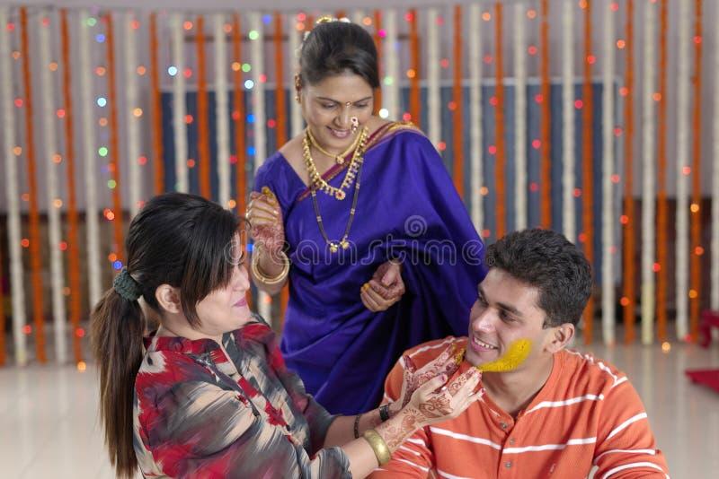 Indischer hindischer Bräutigam mit Gelbwurzpaste auf Gesicht mit Mutter stockbild