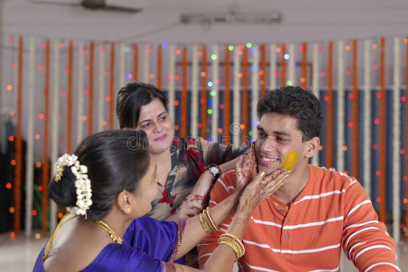 Indischer hindischer Bräutigam mit Gelbwurzpaste auf Gesicht mit Mutter stockbilder