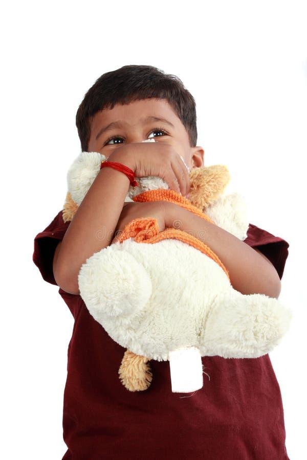 Indischer Junge, der Spielzeug umarmt stockfoto