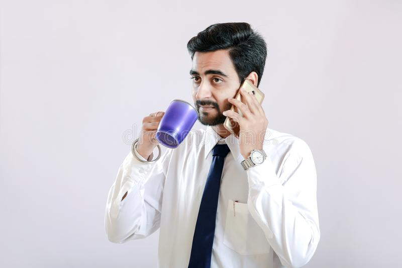 Indischer junger Mann, der auf Mobiltelefon spricht und Schale in der Hand hält lizenzfreie stockfotos