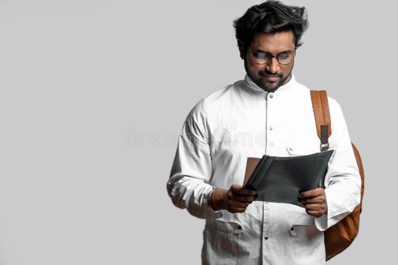 Indischer Kerl bereitet sich für Prüfungen vor lesen Sie Vorträge, Artikel stockfoto