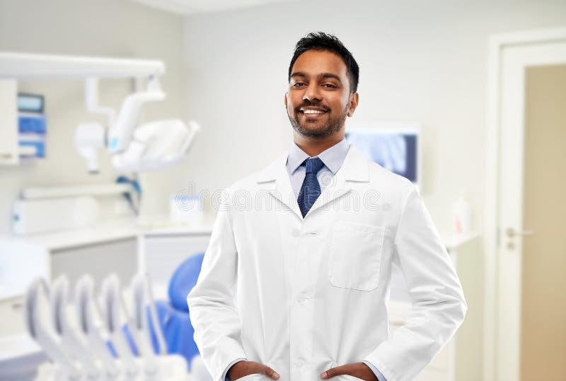 Indischer m?nnlicher Zahnarzt im wei?en Mantel an der zahnmedizinischen Klinik stockbilder