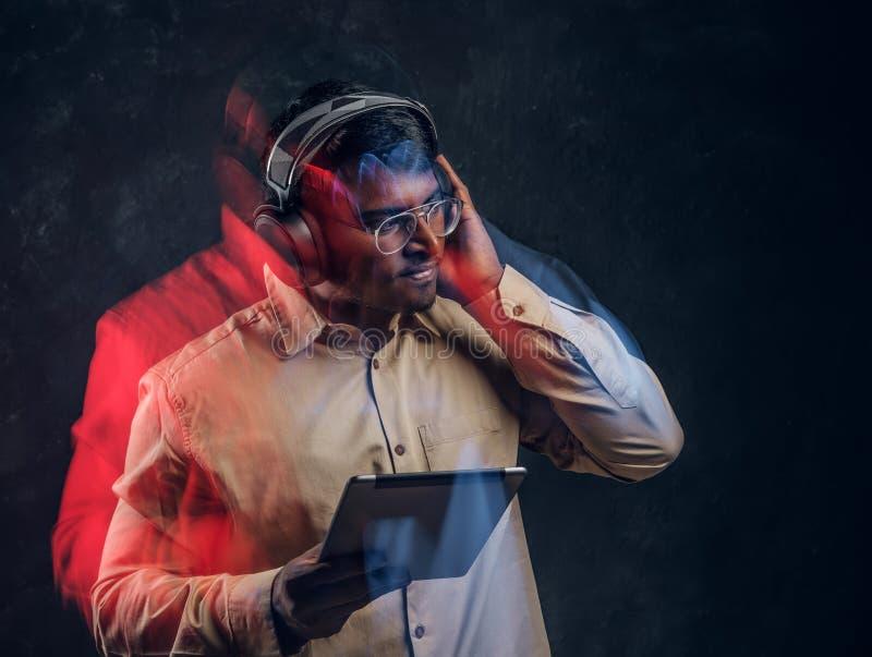 Indischer Mann in den drahtlosen Kopfhörern, die eine Tablette halten und genießt hört seine Lieblingsmusik im Studio lizenzfreies stockbild
