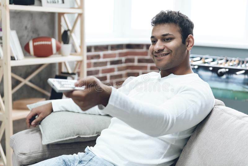 Indischer Mann, der auf Sofa mit Fernbedienung sitzt stockbilder