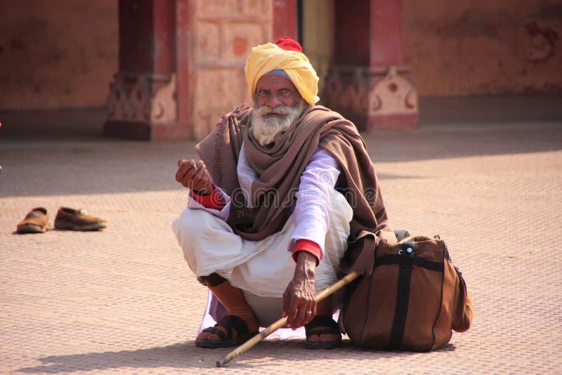 Indischer Mann, der an der Bahnstation, Sawai Madhopur, Indien sitzt stockfoto