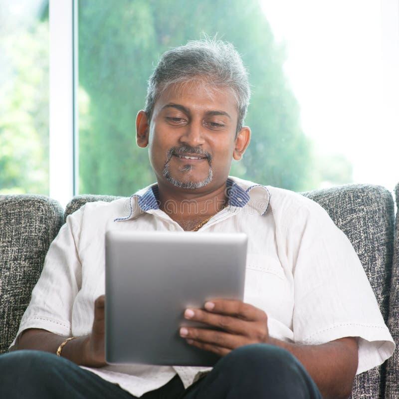 Indischer Mann, der digitalen Tablet-Computer verwendet lizenzfreie stockfotografie
