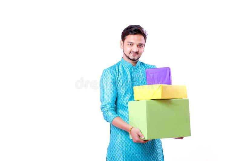 Indischer Mann in der ethnischen Abnutzung und in der Hand in der halten Geschenkbox, lokalisiert über weißem Hintergrund lizenzfreie stockfotos