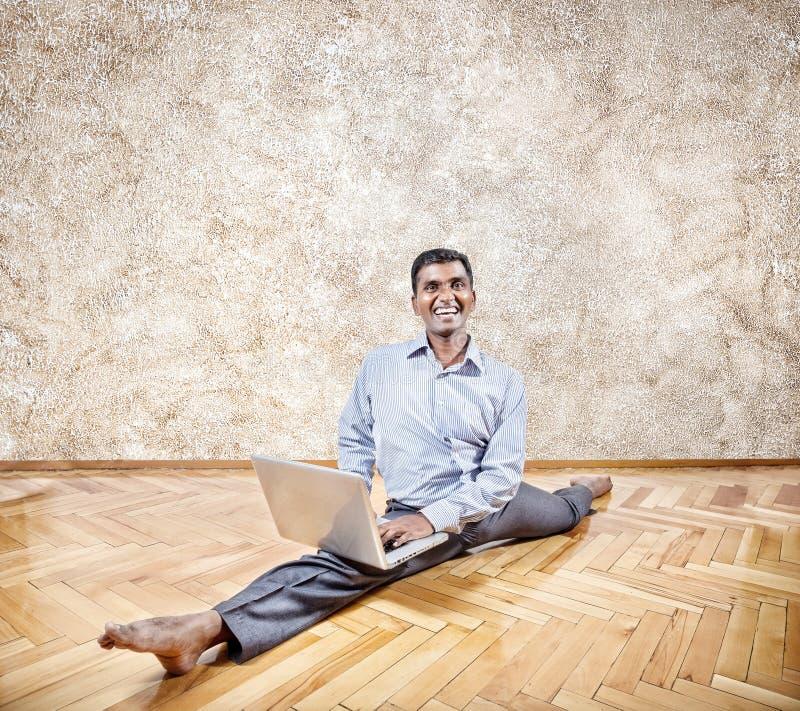 Indischer Mann, der Yoga mit Laptop tut stockbild