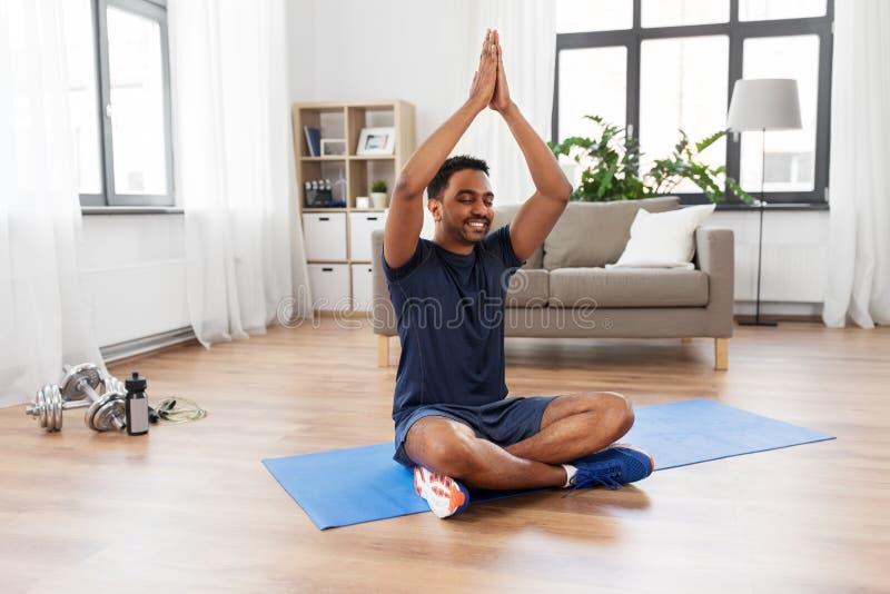 Indischer Mann, der zu Hause in der Lotoshaltung meditiert stockbild