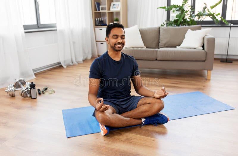 Indischer Mann, der zu Hause in der Lotoshaltung meditiert lizenzfreie stockbilder