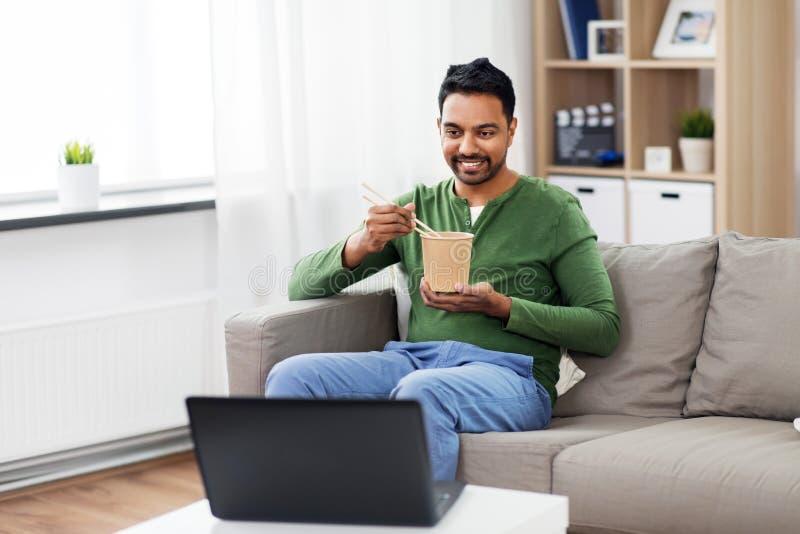 Indischer Mann mit Laptop zum Mitnehmen Nahrung zu Hause essend stockbilder