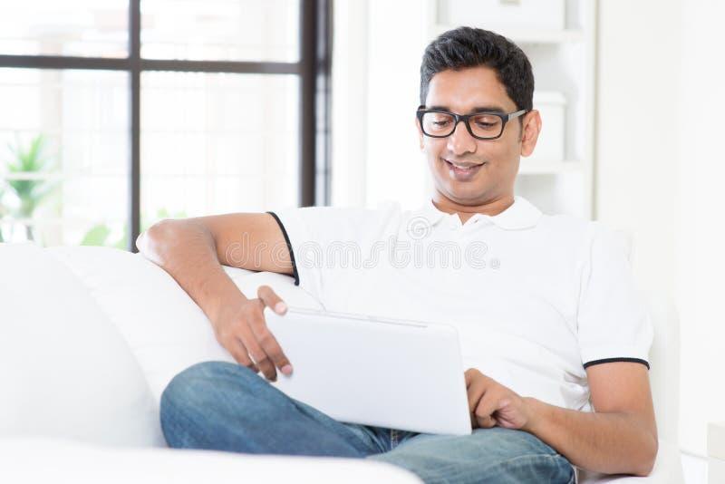 Indischer Mann unter Verwendung der Digitalrechnertablette lizenzfreies stockbild