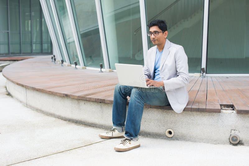 Indischer Mann unter Verwendung des Laptops lizenzfreie stockfotos