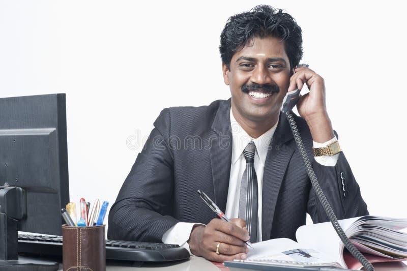 Indischer Südgeschäftsmann, der in einem Büro arbeitet lizenzfreie stockfotos