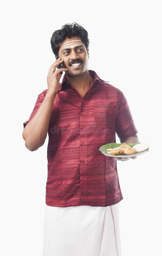 Indischer Südmann, der eine Platte des Lebensmittels hält und auf einem Mobile spricht lizenzfreie stockbilder